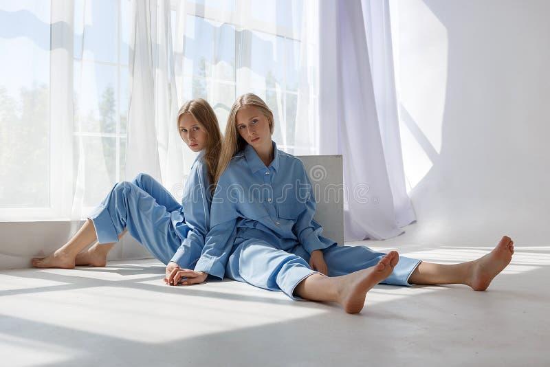 Dwa młodej bliźniaczej dziewczyny siedzi na białej cyclorama podłodze w studiu w wzorze światło i cień w identycznych błękitnych  fotografia royalty free