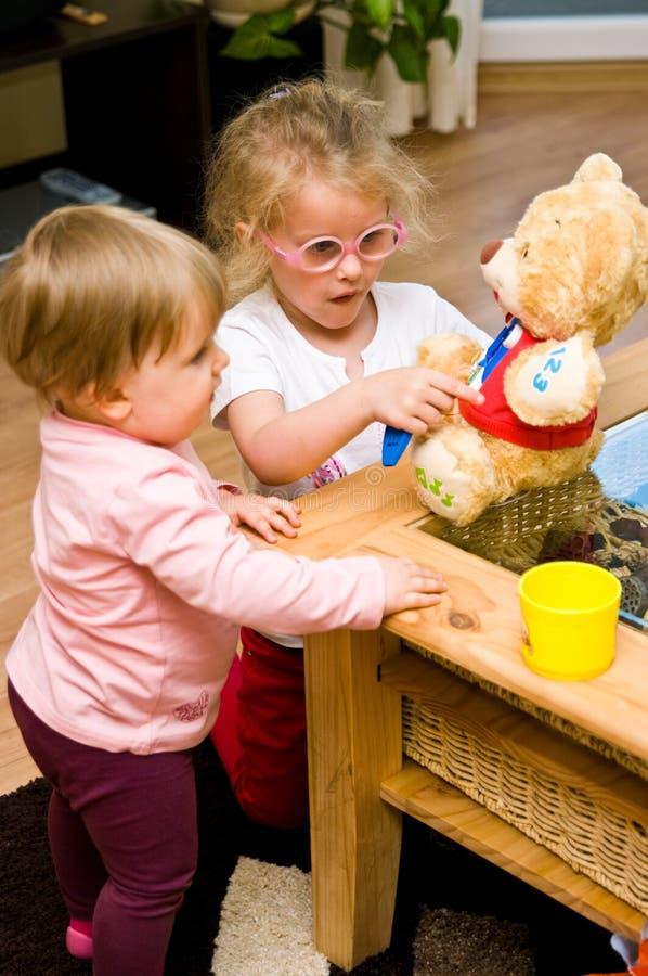 Dwa młodej dziewczyny bawić się z kształcącą niedźwiedź zabawką zdjęcie stock