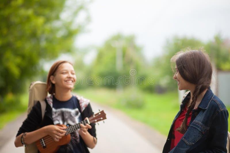 Dwa młodej dziewczyny chodzi wpólnie, śmia się ukulele i bawić się, zdjęcia stock