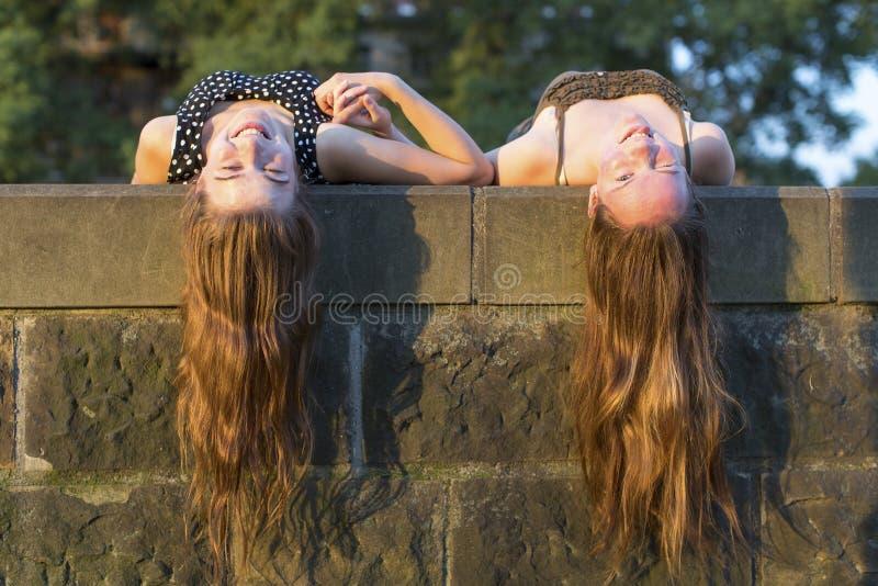 Dwa młodej dziewczyny kłama na kamiennej cegiełce z długie włosy obwieszenie puszkiem zdjęcia royalty free