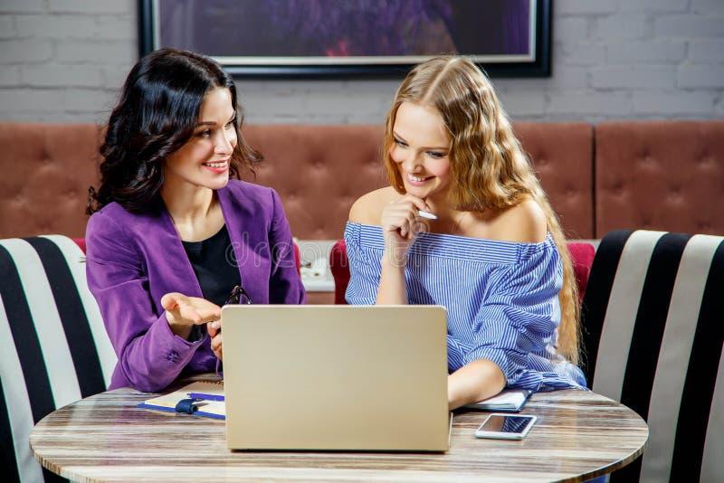 Dwa młodej dziewczyny siedzi przy laptopem podczas gdy dyskutujący biznesowe sprawy fotografia royalty free