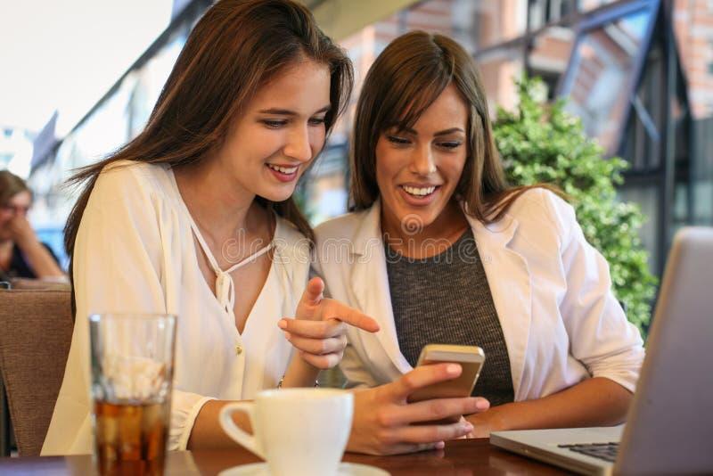 Dwa młodej dziewczyny siedzi w kawiarni używać mądrze telefon obraz royalty free