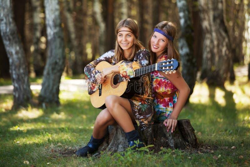 Dwa młodej dziewczyny z gitarą w lato lesie zdjęcie stock