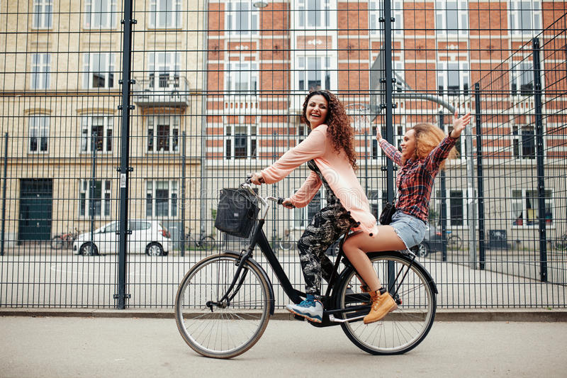 Dwa młodej kobiety cieszy się rower przejażdżkę na miasto ulicie fotografia royalty free