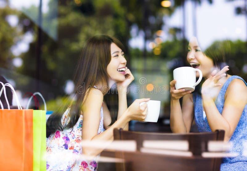 Dwa młodej kobiety gawędzenia w sklep z kawą obraz royalty free