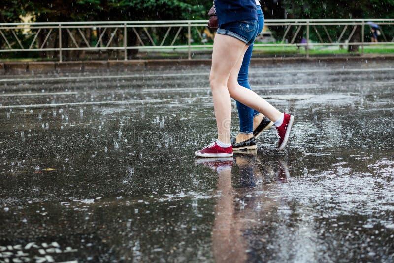Dwa młodej kobiety krzyżuje ulicę w butach iść na piechotę podczas ulewnego deszczu obrazy stock
