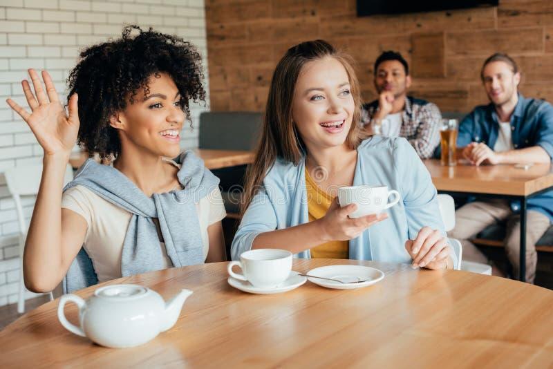 Dwa młodej kobiety ma herbaty w kawiarni i mężczyzna siedzi przy następny stołowy patrzeć obraz stock