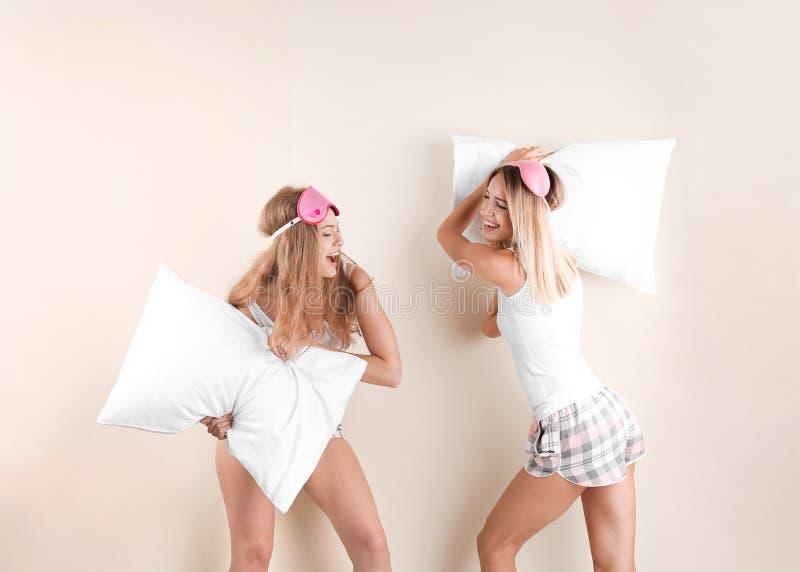 Dwa młodej kobiety ma poduszki walkę obrazy stock
