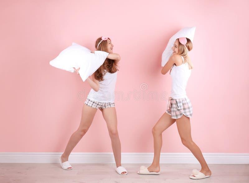 Dwa młodej kobiety ma poduszki walkę blisko izolują fotografia stock