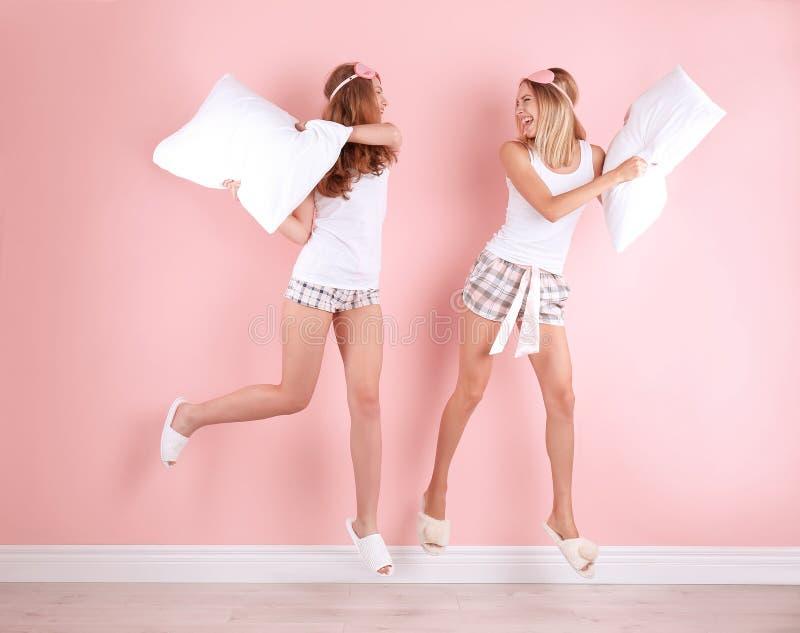 Dwa młodej kobiety ma poduszki walkę blisko izolują zdjęcie royalty free
