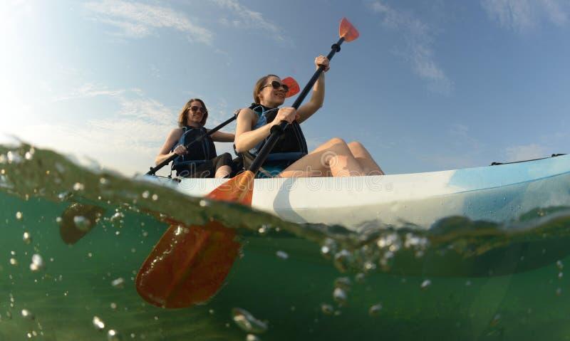 Dwa młodej kobiety paddling błękitnego kajaka zdjęcie royalty free
