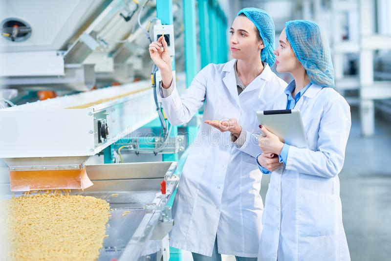 Dwa młodej kobiety Pracuje przy Nowożytną Karmową fabryką zdjęcia royalty free