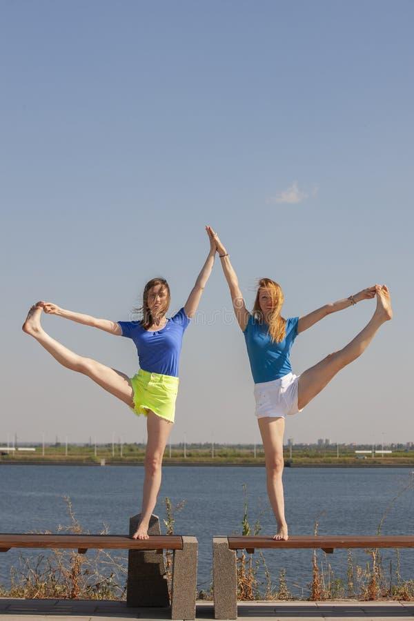 Dwa młodej kobiety robi joga przy naturą Sprawno?? fizyczna, sport, joga i zdrowy stylu ?ycia poj?cie, fotografia stock