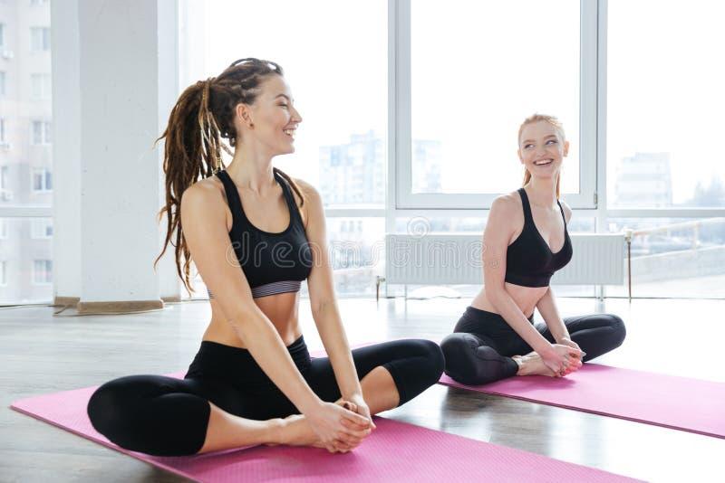 Dwa młodej kobiety rozciąga na różowych joga matach obrazy stock