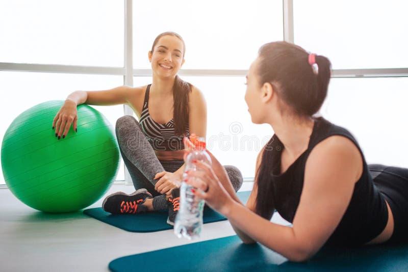 Dwa młodej kobiety siedzą i kłamający na matrass w fintess izbowych I opowiadają zabawę Modele odpoczynek po treningu zdjęcie royalty free