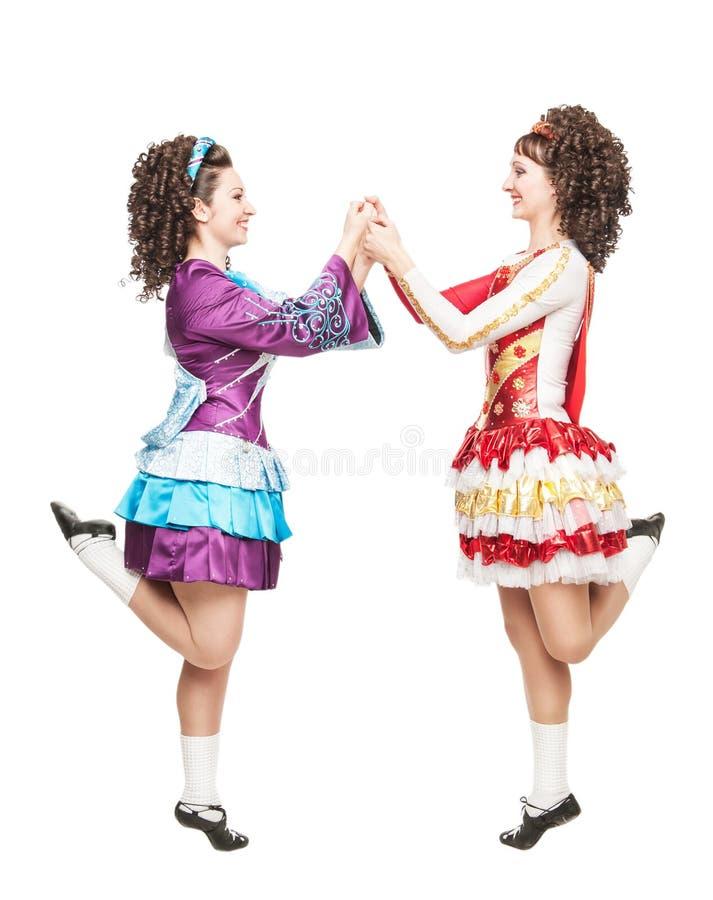 Dwa młodej kobiety w irlandzkim tanu ubierają tana odizolowywającego obraz stock