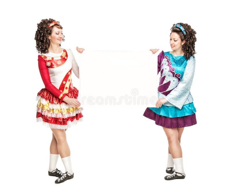 Dwa młodej kobiety w irlandzkim tanu ubierają z pustym papierem fotografia stock