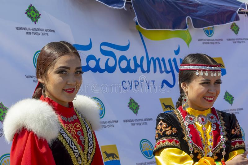 Dwa młodej kobiety w krajowych Bashkir ubraniach za one i język «Sabantuy Surgut « zdjęcie stock