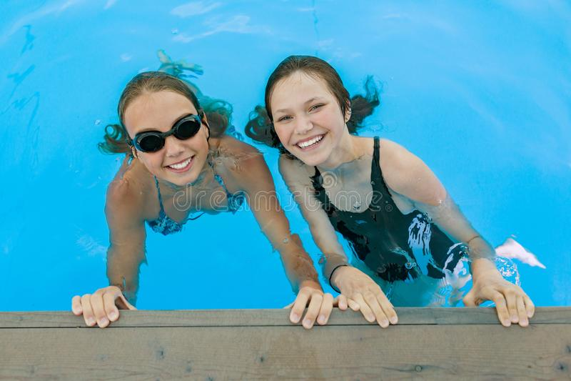 Dwa młodej nastoletniej dziewczyny ma zabawę w pływackim basenie obrazy stock