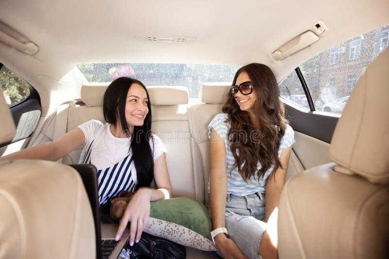Dwa młodej one uśmiechają się pięknej dziewczyny z długie włosy, ubierają w przypadkowym stylu, siedzą w tylnym siedzeniu samochó obrazy stock