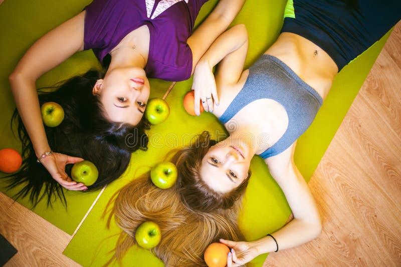 Dwa młodej sportowej budowy ciała kobiety w gym kłamstwie na podłoga na joga matują zdjęcie stock
