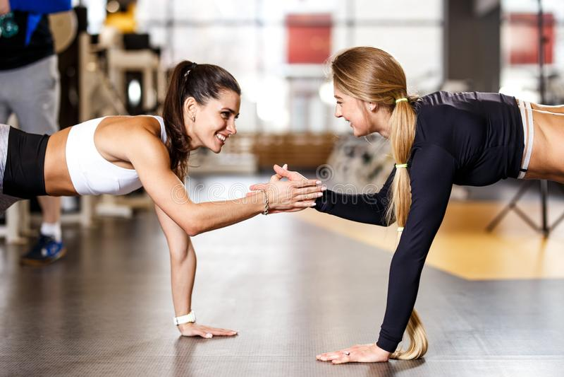 Dwa młodej sportowej dziewczyny ubierającej w sportswear robią desce i trzymają ręka w rękę w nowożytnym gym obraz royalty free