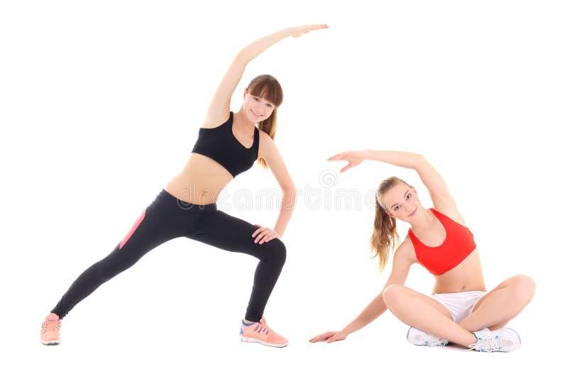 Dwa młodej sporty kobiety robi rozciąganiu ćwiczą nad bielu plecy zdjęcia stock
