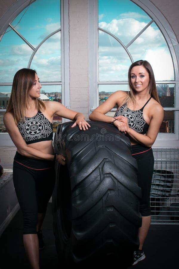 Dwa młodej sprawności fizycznej kobiety odpoczywa na oponie obrazy stock