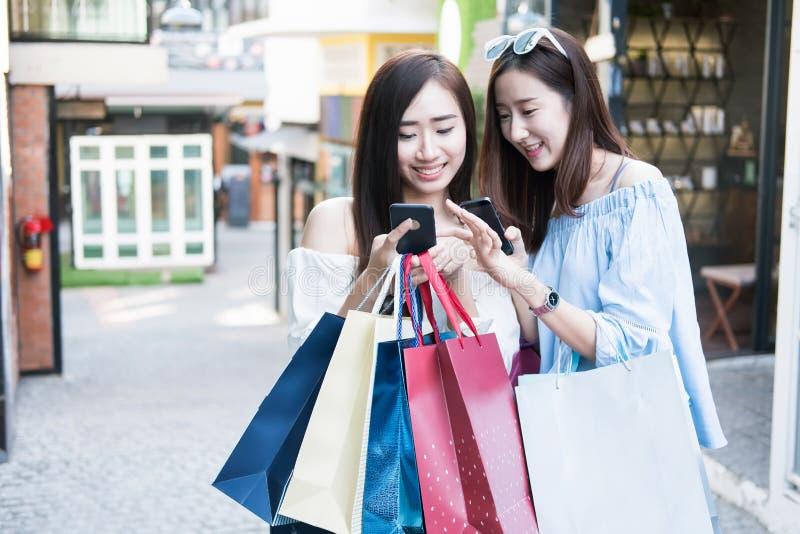 Dwa młodej szczęśliwej azjatykciej kobiety robi zakupy plenerowego zakupy centrum handlowe zdjęcia royalty free