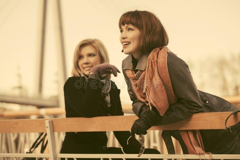 Dwa młodej szczęśliwej mody kobiety na ławce w miasto ulicie zdjęcia stock