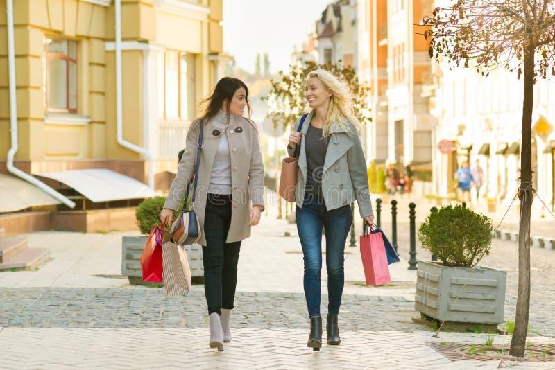 Dwa młodej uśmiechniętej kobiety na miasto ulicie z torbami na zakupy, pogodny jesień dzień zdjęcia royalty free
