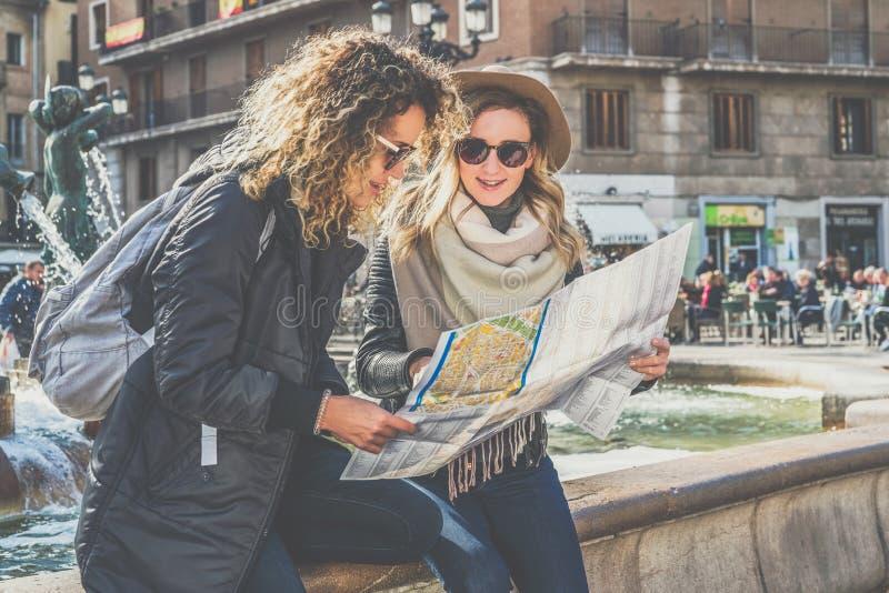 Dwa młodej uśmiechniętej turystycznej kobiety siedzą na miasto ulicznej pobliskiej fontannie i są przyglądający dla sposobu na ma fotografia royalty free