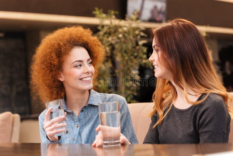 Dwa młodych kobiet szczęśliwa atrakcyjna woda pitna w kawiarni obraz royalty free