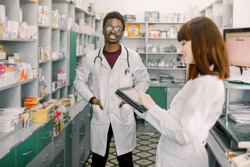 Dwa młodych rozochoconych farmaceut Afrykański mężczyzna i Kaukaska kobieta pracuje wpólnie Kobieta u?ywa pastylk? farmaceuty obrazy royalty free