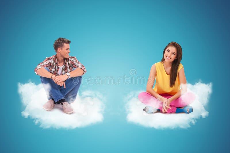 Dwa młodzi ludzie siedzi i odpoczywa na couds zdjęcia stock