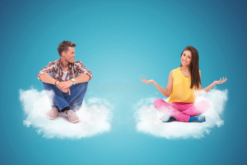 Dwa młodzi ludzie siedzi na chmur witać zdjęcie stock