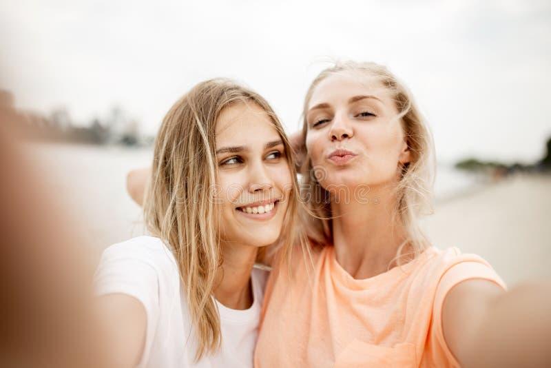 Dwa m?odej ?adnej blondynki dziewczyny bior? selfie na pla?y na ciep?ym wietrznym dniu zdjęcia royalty free