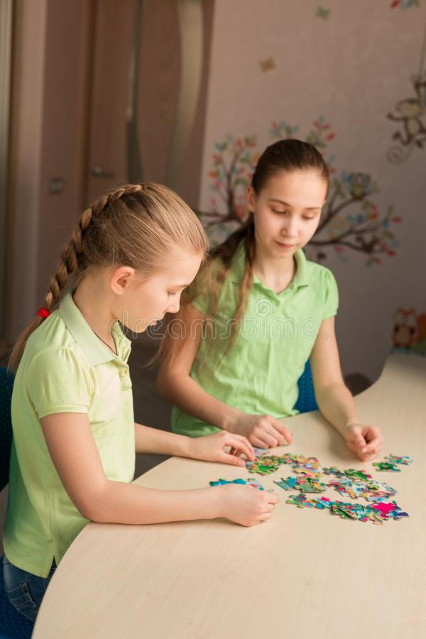 Dwa małej dziewczynki rozwiązuje łamigłówkę wpólnie fotografia royalty free