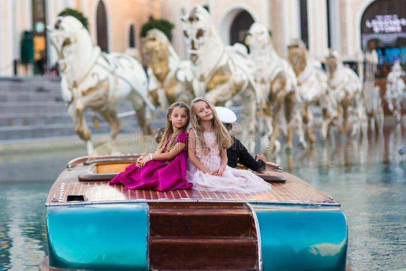 Dwa małej pięknej dziewczyny w luksusowych modnych sukniach siedzą na łodzi na wakacje Dziewczyn pozować zdjęcia stock