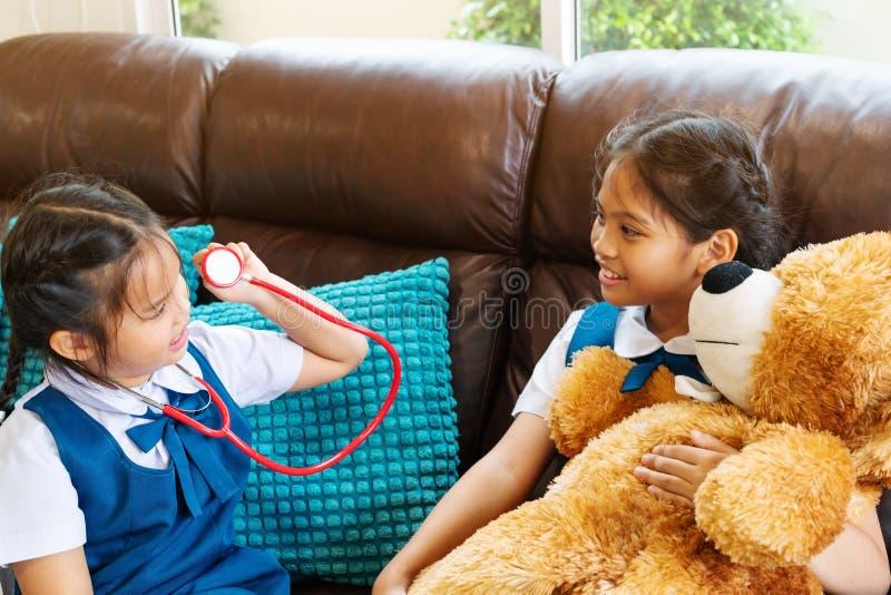 Dwa mała dziewczynka jest uśmiechnięta i bawić się lekarkę z stetoskopem Dzieciak i opieki zdrowotnej pojęcie obrazy stock