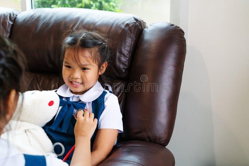 Dwa mała dziewczynka jest uśmiechnięta i bawić się lekarkę z stetoskopem Dzieciak i opieki zdrowotnej pojęcie fotografia royalty free