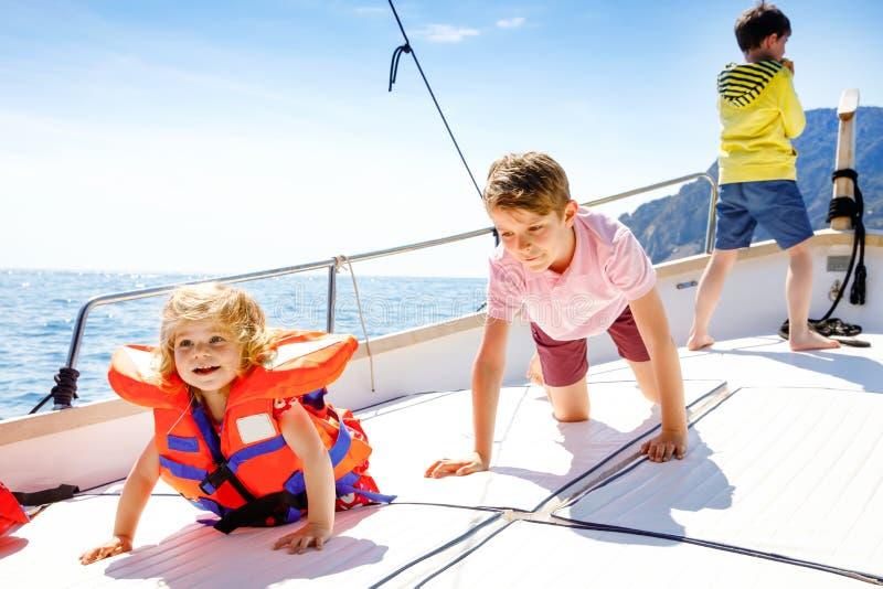 Dwa małe dziecko chłopiec i berbeć dziewczyna cieszy się żeglowanie łódź one potykają się Rodzinni wakacje na oceanie lub morzu n zdjęcia royalty free