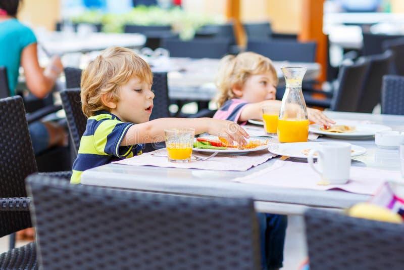 Dwa małe dziecko chłopiec ma zdrowego śniadanie w hotelowej restauraci zdjęcie royalty free