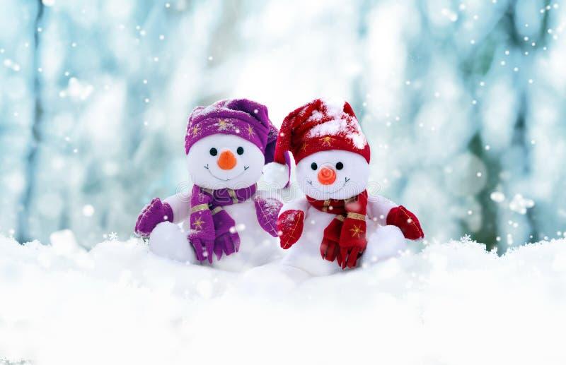Dwa małego bałwanu dziewczyna i chłopiec w nakrętkach i szalikach na śniegu w zimie Tło z śmiesznym bałwanem wi?cej toreb, ?wi?t  zdjęcie stock