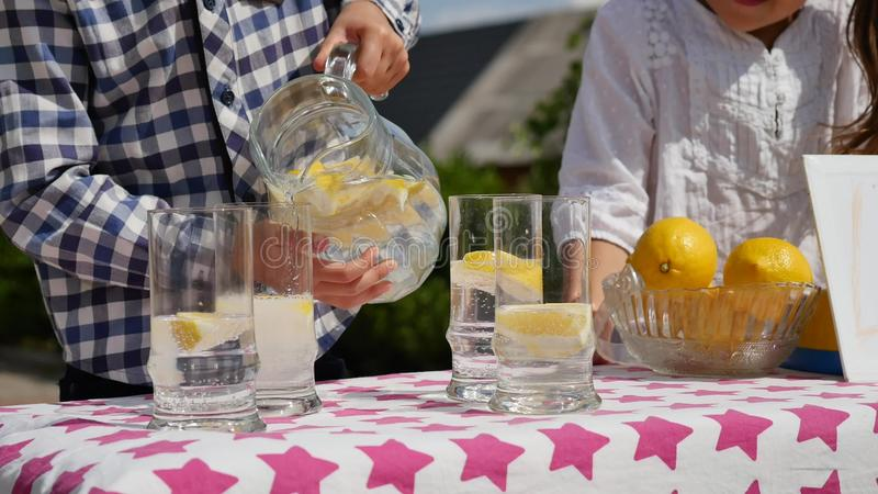 Dwa małego dziecka sprzedają lemoniadę przy domowej roboty lemoniada stojakiem na słonecznym dniu z cena znakiem dla przedsiębior zdjęcia royalty free