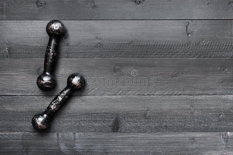Dwa małego rocznika dumbbells na czarnej drewnianej podłoga zdjęcia royalty free