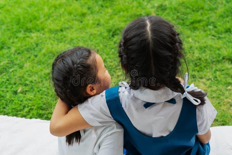 Dwa małej azjatykciej dziewczyny siostry ściska szczęśliwą poczta w mundurku szkolnym szkoły pojęcie, z powrotem zdjęcia royalty free