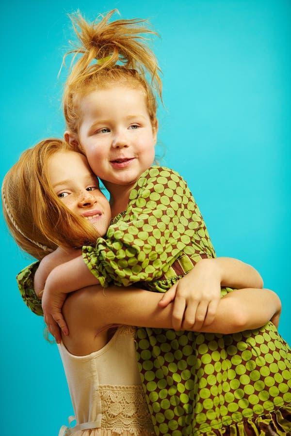 Dwa małej czerwonej głowiastej dziewczyny siostry ściskają związek miłość i opiekę each innego miłych, ekspresowych, obraz royalty free