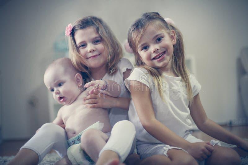 Dwa małej dziewczynki dbają dziecko brata zdjęcia stock