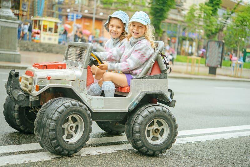 Dwa małej dziewczynki jedzie zabawkarskiego samochód zdjęcie stock